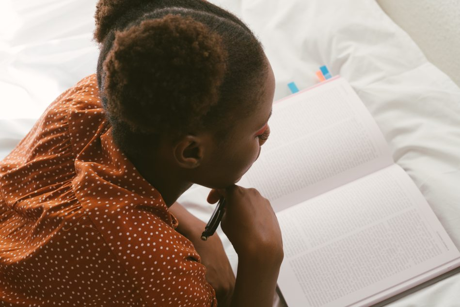 Image of a young woman reading a textbook on a bed