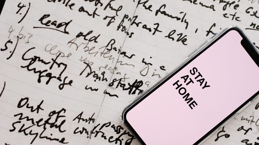 "Image of a notebook with hand writing. A smartphone that displays ""stay at home"" on the screen"