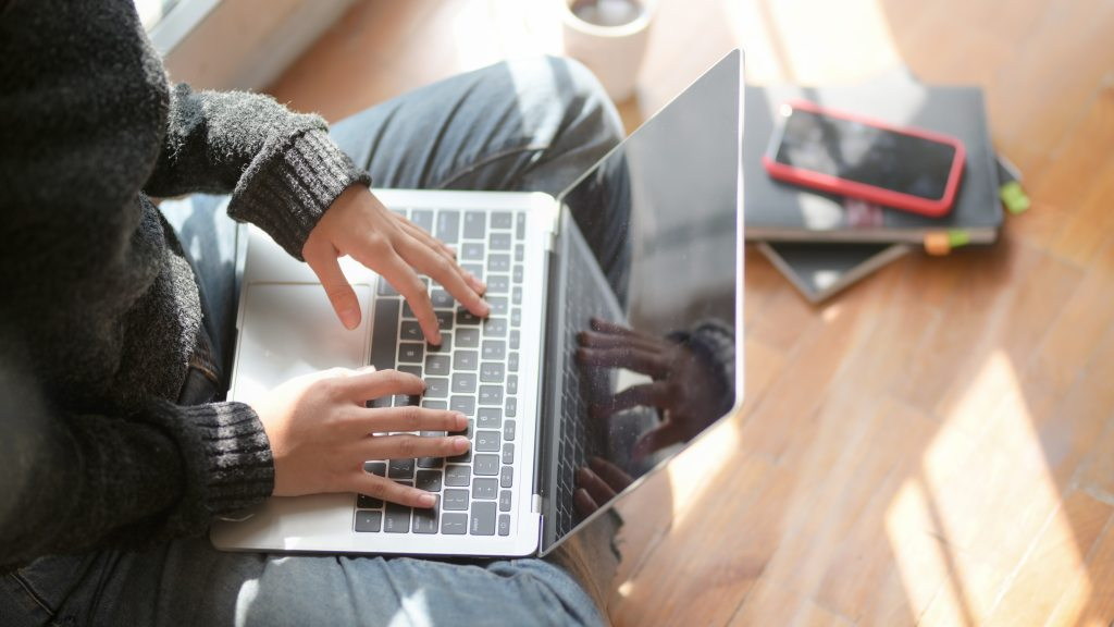Image of young woman sitting on the floor and working on laptop